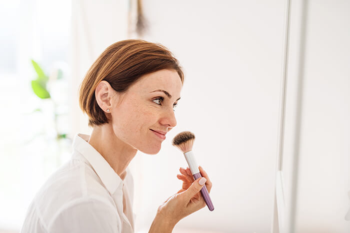 woman applying make-up on her face