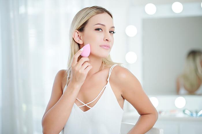 woman blending face foundation