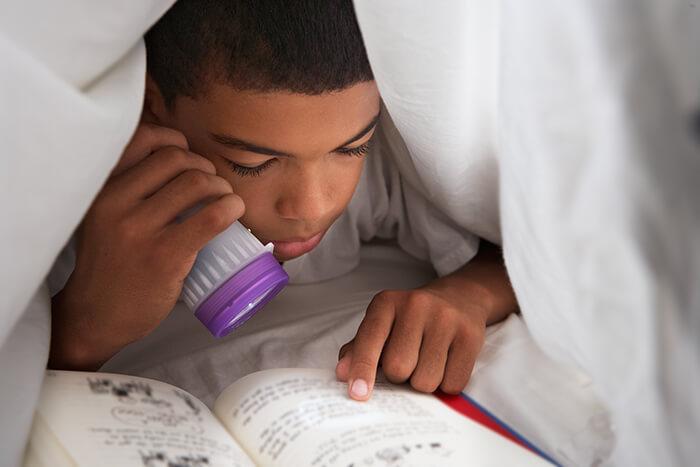 boy-reading-book-with-torch-under-duvet