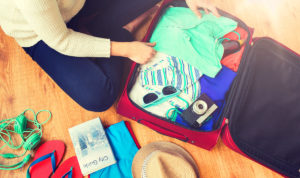 woman packing travel bag for vacation