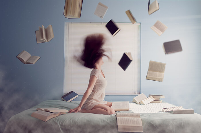 angry woman sitting on bed with flying books