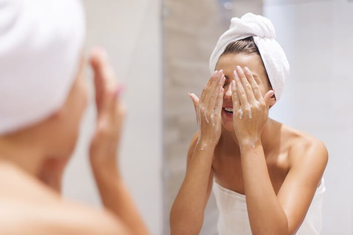 woman washing face in the bathroom